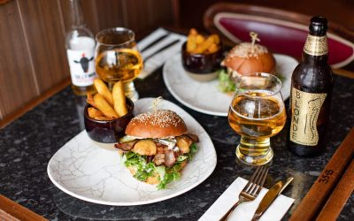 table laid out with two burgers with chips on side and two beers