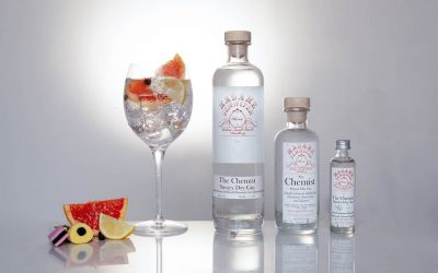 Three different sized bottles of Madame Jennifer gin and a large gin goblet with pink grapefruit garnish