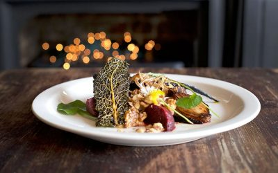 A plate of food with a crisped piece of kale photographed with fairy lights in the background