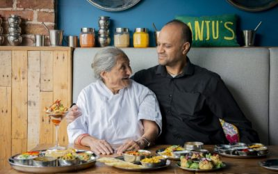 Naimesh and his mother Manju at Manjus Brighton, stood next to a countertop full of food.