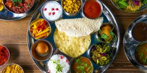 Indian Thali tray with dips, poppadoms and curries
