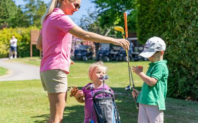 Two children are being shown how to play gold, a woman in a pink t-shirt is handing a club to a boy in a green t-shirt and cap, the second child is stood with the golf club bag.