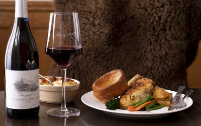 A dark wood table has on it a plate of Sunday lunch, a bottle and glass of red wine and a side of cauliflower cheese