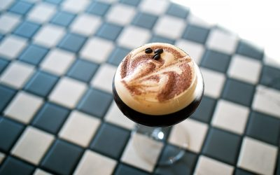 Esprosso martini with latte art and fresh coffee beans, photographed against a black and white chequered floor.