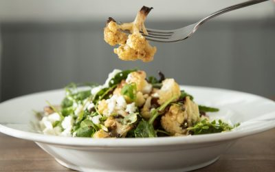 Baked cauliflower salad with feta cheese served in a white dish with a fork picking up a piece of cauliflower.