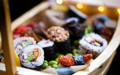 A wooden model ship displaying a selection of colourful sushi rolls on a bed of edamame beans.