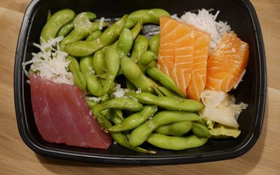 Salmon and tuna sashimi box with edamame beans.
