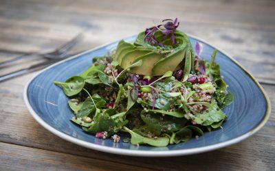 A leafy salad with spinach, sprouts and thinly sliced avocado. Served on a blue triangular plate on a wooden table.
