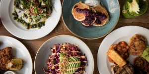 A selection of brunch meals laid out on a wooden table. Including an avocado salad and blueberry pancakes.