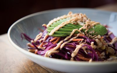 Red cabbage salad with sliced avocado and sauce in a grey bowl