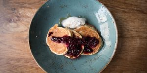 American style pancakes with a blueberry compote and cream, drizzled with maple syrup. Served in a duck egg blue ceramic dish on a wooden table.