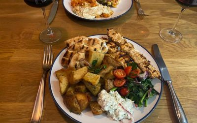 Plates of seared smoky chicken skewers with chunky chips, tzatziki and pitta served at home.
