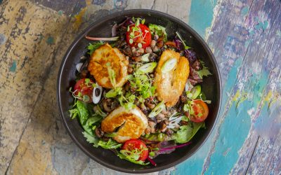 An overhead shot of a plate of halloumi and salad in a dark deep bowl on a painted distressed table