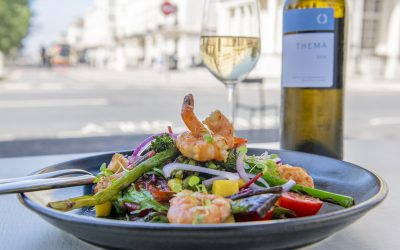 A black dish of large prawns with seasonal roasted vegetables and a bottle of white wine.