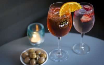 Glasses of Aperol Spritz with a small bowl of fresh olives and a tealight