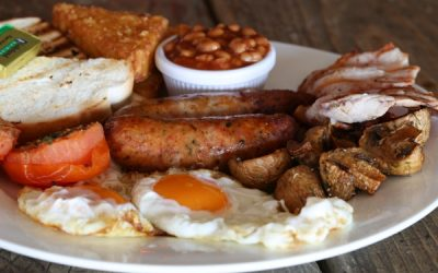 Full English breakfast with fried egg, a pot of beans, hash browns, bacon and sausage.