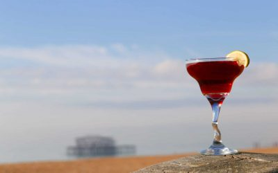 A bright red cocktail in a glass with a wobbly stem garnished with a wedge of lime. Photographed on the beach with the West Pier in the background.
