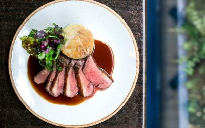 Sliced rare meat with fondant potatoes and a rich gravy. Served on a white ceramic plate with a brown glazed edge.