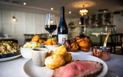 Roast beef and roast potatoes on a plate with a small pot of gravy, in the background there are bowls of vegetables, Yorkshire puddings and an open bottle of red wine with a glass full next to it.