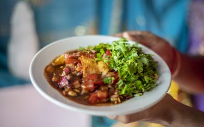 A plate of samosa chaat with generous quantities of coriander being held in front of a turquoise sari