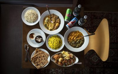 Overhead shot of Indian feast including curries, rice, naan and drinks