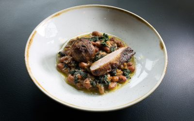 A rustic shallow bowl with a slice of meat on a bead of bean & kale stew.