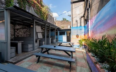 garden with tables and benches and seating area on the side with cover above, wall painted in different colors