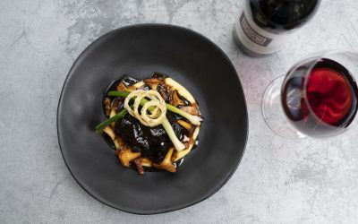 An overhead shot of a dark grey ceramic bowl with orange and brown mushrooms and spring onions. The bowl is on a light grey stone table and in the top right corner there is a partial view of a bottle of wine and a glass of red wine