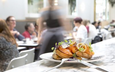 Smoked salmon brunch plate sat on the bar with a busy restaurant in the background