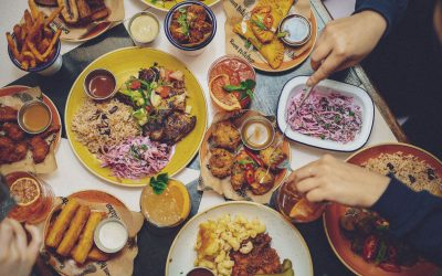 overhead shot of a table filled with Caribbean food, slaw, fried plantain, rice and peas and cocktails.