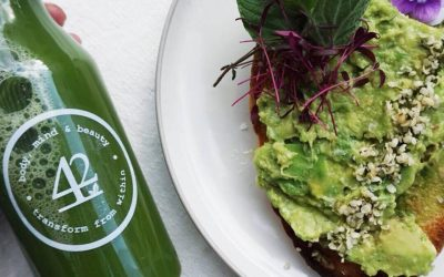 A plate of sliced avocado on toast with a bottle of freshly squeezed juice.