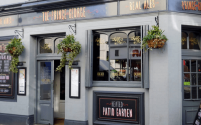 Exterior shot of the entrance of The Prince George. Displaying blooming hanging baskets against the grey and black paintwork.