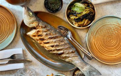 Whole grilled fish on a plate with sides and cutlery