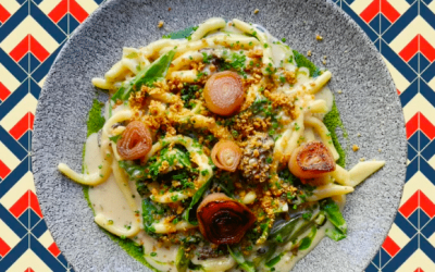 Creamy pasta dish with herb oil served on a ceramic plate against a printed table cloth.