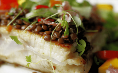 A close up photo of a piece of white fish topped wit puy lentils and garnished with microgreens.