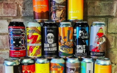 Craft ale cans piled up in front of a brick wall