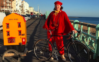 Lady dressed in red with a bicycle and house shaped trailer next to Brighton beach