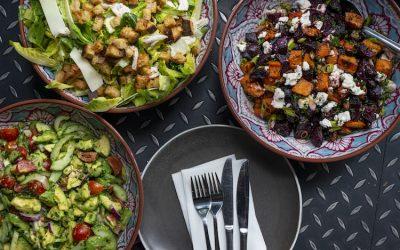 Bowls of salads including a roasted vegetable salad, an avocado salad and a caesar salad.