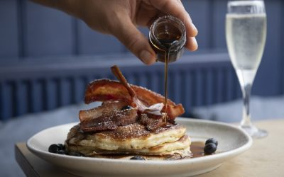 A stack of pancakes with bacon and maple syrup being poured over from a small glass pot. Served with a glass of fizz.
