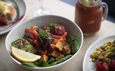A vegan breakfast bowl with avocado and roasted vegetables. Served with a bloody Mary with a stick of celery.