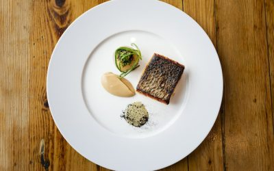 Pan fried white fish with a sauce and side accompaniments