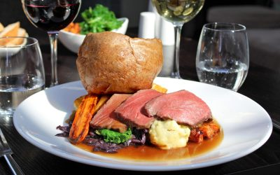 Slices of rare roast beef sat seasonal vegetables with a large Yorkshire pudding and gravy. Photographed outside on a sunny day with a glass of wine.