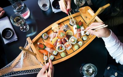 Sushi feast served on a wooden boat platter with people using chopsticks to pick pieces of sushi.