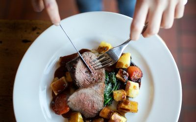 Sunday roast beef with cubed roasted root vegetables and a rich gravy. Hands featured in the shot holding a knife and fork.