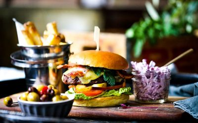 A colourful photo of a large burger stacked with burger, salad and cheese. Served with red cabbage slaw and a bucket of chips.