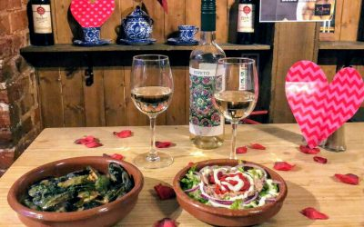 A valentine's table with two glasses of white wine and terracotta bowls of tapas food.