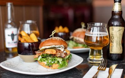 table laide out with chips and burger on one pate and glass of the beer with opened beer bottle