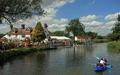 Landscape photo of The Anchor Inn next to the river with people kayaking in the water.