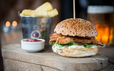 A chicken burger and chips with a pot of sauce served on a wooden board alongside a pint of beer.