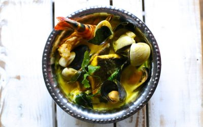 A metal bowl of seafood curry with prawns and mussels